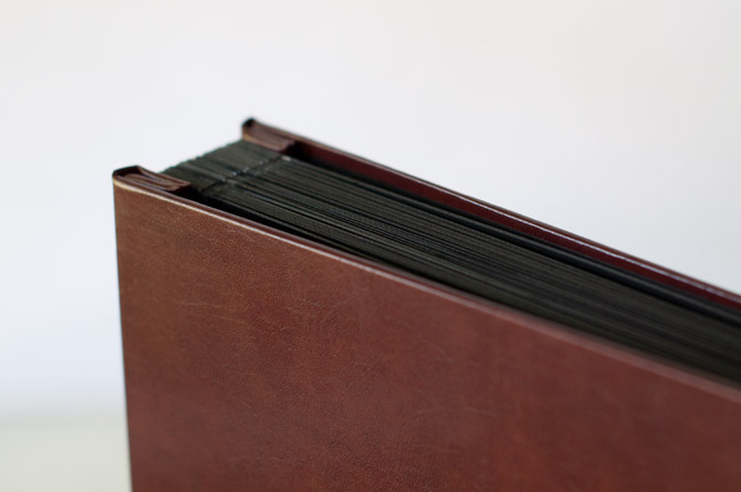 brown leather post bound album with black pages