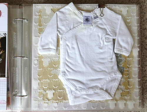 Scrapbook baby's first onesie to remember just how small they were when you first brought them home (via Allie Edwards)